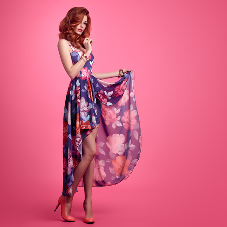 패션 관능적 인 섹시한 빨간 머리 모델 패션 포즈. 여름 옷에 아름다움 여자입니다. 트렌디 한 꽃 드레스, 세련된 컬리 물결 형 헤어 스타일, 고급 패션