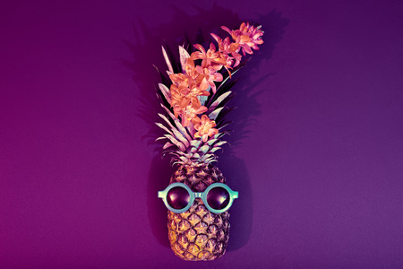 Tropical pineapple with Disco Sunglasses, flower. Pineapple Fruit Fashion Hipster. Beach Fun Art Style.Minimal.Night club.Hot Summer Glamour Beach Vibes. Zdjęcie Seryjne