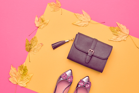 Autumn Arrives. Fall Fashion Glamour Lady Look.Trendy Handbag Clutch. Fashion Stylish Glamour Shoes. Yellow Autumn Fall Leaves on Pink