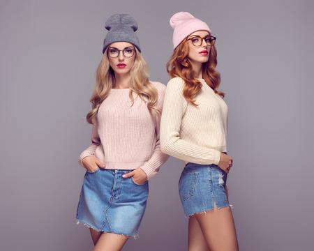 Moda. Gemelos bonitos de los mejores amigos de las hermanas. Mujer hermosa joven en traje con estilo del invierno del otoño. Refresque el modelo de Hipster en el suéter acogedor, vidrios de Glamour. Juguetón Rubio Redhead Girls en sombrero de moda gorrita Foto de archivo - 86037973