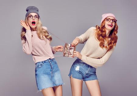 若い女性は、笑顔を驚かせた。狂気の楽しいを持っています。ファッション。かなり最高の友達双子姉妹スタイリッシュなファッション秋冬の服装