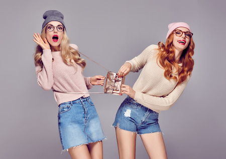 Young Woman Surprised Smiling. Having Fun Crazy. Fashion. Pretty Sisters Best Friends Twins in Stylish fashion Autumn Winter Outfit. Playful Hipster Girls. Cool Blond Redhead in Cozy Sweater, Glasses