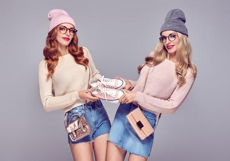 Mujer joven que se divierte loco. Moda. Concepto de descuento de ventas de compras. Pretty Sisters Best Friends Twins en elegante traje de otoño invierno. Chica juguetona modelo inconformista en puente acogedor, gafas Foto de archivo - 86257660