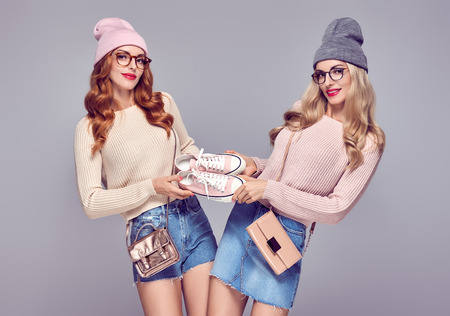 Young Woman Having Fun Crazy. Fashion. Shopping Sales Discount concept. Pretty Sisters Best Friends Twins in Stylish fashion Autumn Winter Outfit. Playful Hipster Model Girl in Cozy Jumper, Glasses