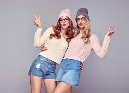 M?oda kobieta zabawy Crazy dmuchanie warg zrobi? Air Kiss. Moda. Pretty Sisters Najlepszymi przyjaci�?mi bli?niak�w w modnej mody Autumn Winter Outfit. Playful Dziewczyny Hipster. Cool Model w Cozy Sweter, Okulary