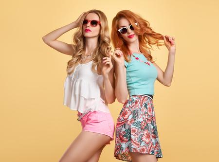 Moda. M?oda Kobieta O Zabawa. Hipster w eleganckim stroju. Siostry Best Friends Twins Crazy. Happy Pretty Girl w modzie Stylowa Zimowe okulary s?oneczne, modne Fryzura. Model Playful Mi?kkie U?miecha Si?