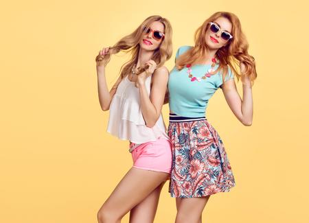 M?oda Kobieta O Zabawa. Moda. Hipster w eleganckim stroju. Siostry Best Friends Twins Crazy. Happy Pretty Girl w modzie Stylowa Zimowe okulary s?oneczne, modne Fryzura. Model Playful Mi?kkie U?miecha Si?