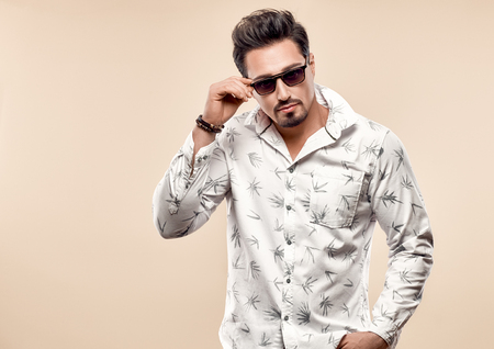 Handsome young Fashion man in Trendy Sunglasses. Sporty Confident Brunette Bearded guy in white shirt, Stylish Hairstyle, Summer Elegant Outfit. Studio fashion portrait on light background