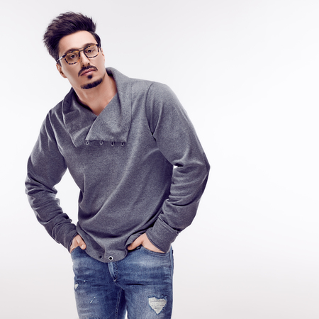 Handsome young Fashion guy. Autumn Trendy Outfit, Glasses. Sporty Confident Brunette Bearded man with hands in pockets. Stylish Hairstyle, fashionable gray jumper. Studio fashion pose,white background Zdjęcie Seryjne