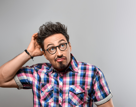 ハンサムな若い男と考えているアイデア、クレイジーです。トレンディなシャツ、メガネで肖像画のヒップスター オタク敗者男。ブルネットの感情