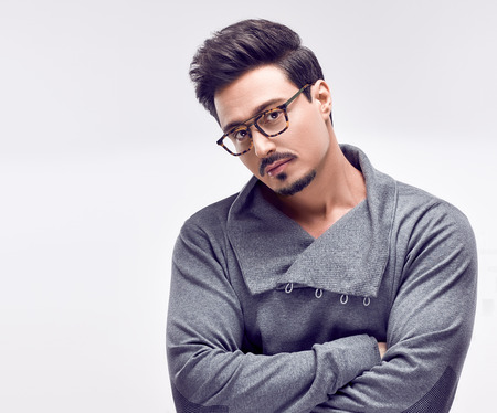 Handsome young Fashion guy. Autumn Trendy Outfit, Glasses. Sporty Confident Brunette Bearded man in fashionable gray jumper, Stylish Hairstyle. Studio fashion portrait on white background