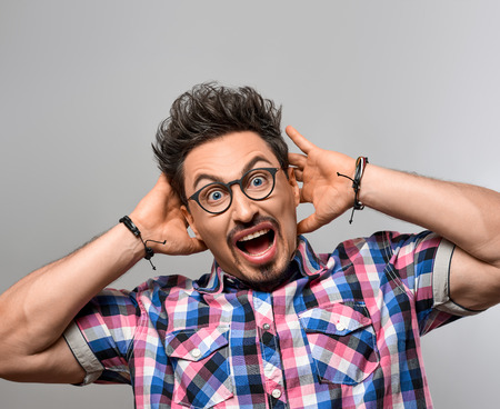 Young man Screaming Holding his head. Having Fun Yell Crazy, Open Mouth. Portrait Handsome Hipster guy in Trendy shirt, Glasses. Brunette Bearded Emotional man, Stylish fashion Hairstyle. Blue Eyes Zdjęcie Seryjne