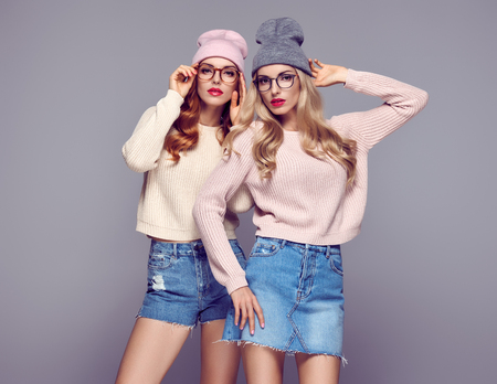 Fashion. Pretty Sisters Best Friends Twins. Young beautiful woman in Stylish Autumn Winter Outfit. Cool Hipster Model in Cozy sweater, Glamour glasses. Playful Blond Redhead Girls in Trendy Beanie hat Stock Photo