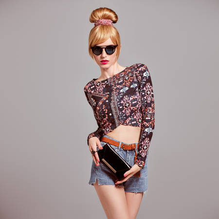 Fashion. Sexy model Girl, cheeky Emotion. Young Woman in Glamour Sunglasses, Stylish Hairstyle, fashion Autumn Outfit. Beautiful Blond Woman with Trendy Glamour Handbag Clutch, fashion pose Stock Photo
