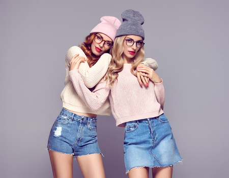 Fashion. Young Beautiful woman in Stylish Autumn outfit Hugging. Pretty Sisters Best Friends Twins. Hipster Blond Redhead Model, fashion Cozy jumper, Glasses. Girls in Trendy Beanie hat.Vanilla color Stock Photo