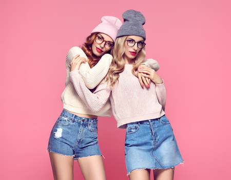 Fashion. Young woman Hugging in Stylish Autumn outfit. Pretty Sisters Best Friends Twins. Hipster Blond Redhead Model, fashion Cozy jumper, Glasses. Beautiful Girls in Trendy Beanie hat on Pink Stock Photo