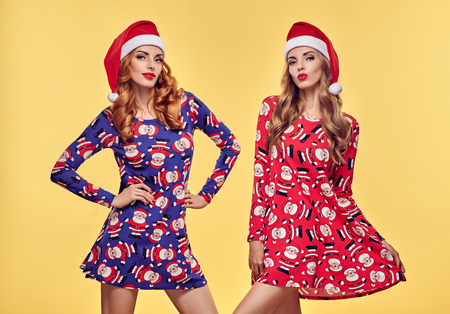 Christmas New Year. Young Woman in Santa Claus hat Having Fun Happy Smiling. Fashion. Pretty Playful Sisters Best Friends. Twins in Stylish fashion Red Xmas Holiday Dress on Yellow. Christmas Colorful