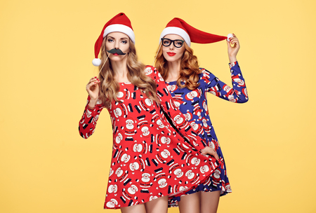 Christmas New Year. Young Woman in Santa Claus hat Having Fun Happy with Holiday Props. Fashion. Pretty Playful Sisters Best Friends.Twins in Stylish fashion Red XmasDress on Yellow.Christmas Colorful