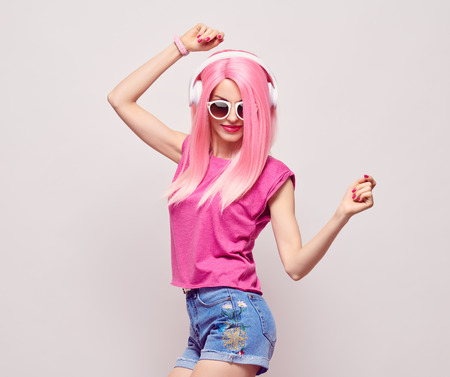 DJ Girl Hipster with Pink Fashion Hairstyle Dance. Young Playful Model Woman in Trendy Headphones Smiling. DJ Music vibrations, Clubbing. Party Style Banco de Imagens