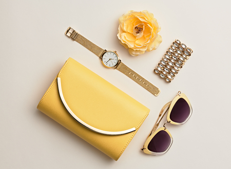 Fashion. Minimal Style. Woman Accessories Set. Flat lay. Trendy fashion Clutch, Glamour Summer Sunglasses. Flower. Luxury Spring lady. Yellow Pastel Color