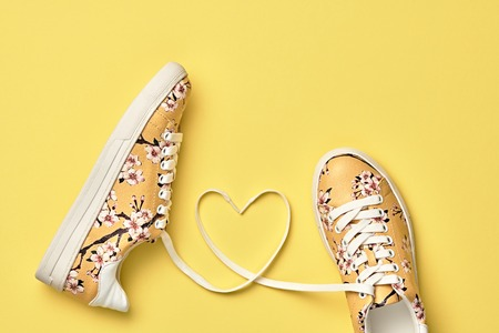 心とファッションのトレンディなトレーナー。愛、流行に敏感なセット。パステル カラー。最小限のスタイル。黄色の夏の花のスニーカー。フラッ