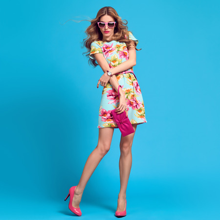 Fashion Young woman in Floral Dress. Sexy Blond Lady in fashion pose. Trendy, Stylish Hairstyle, fashion Sunglasses, Glamour Heels. Playful Girl, Spring Summer Outfit
