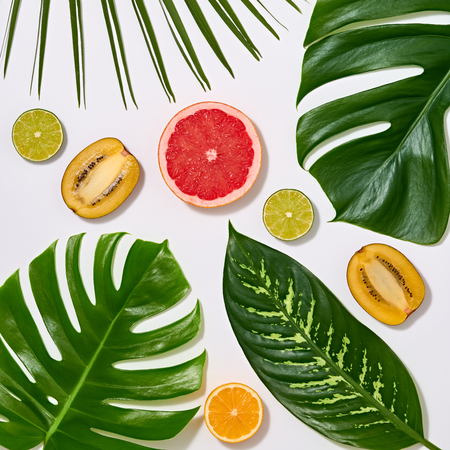 Creative Tropical Layout. Palm Leaves and Fresh Fruits. Colorful Summer Design Set. Healthy Art Food concept. Nature Bright Summer background. Minimal. Stock Photo