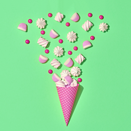 Marshmallow, Meringue background. Ice Cream Cone with Gummy Candies Sweets. Flat lay. Summer Party, Birthday Firework. Bright Color. Trendy fashion Style. Minimal. Art