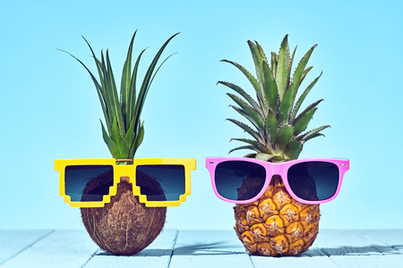Tropical Pineapple and Coconut. Bright Summer Color. Two Hipster Fruits in Trendy Sunglasses. Fashion Style. Creative Minimal. Hot Beach Vibes. Summer party Mood Stock Photo