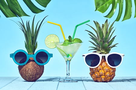Tropical Pineapple and Coconut. Bright Summer Color. Two Hipster Fruits in Trendy Sunglasses, Cocktail on Beach. Fashion Style. Creative Art. Hot Summer party Mood
