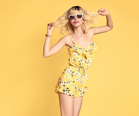Short-haired girl in Fashionable Sunglasses Dancing. Young Playful female Blond model in Stylish fashion Summer Outfit. Beautiful Happy woman Having Fun dance in Studio on Yellow