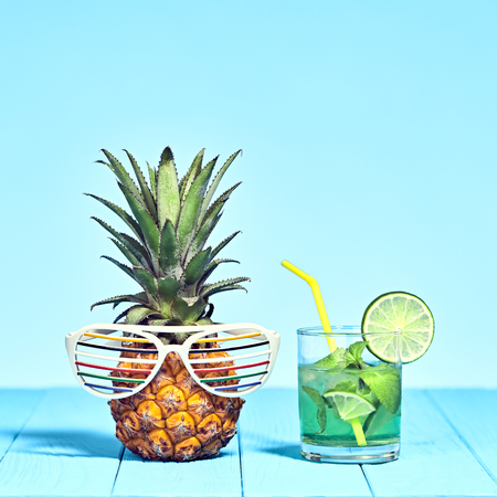 Tropical Pineapple Hipster with Cocktail on Beach. Bright Summer Color. Trendy fashion Style. Hot summer Vibes. Creative Art. Fun party Mood. Minimal