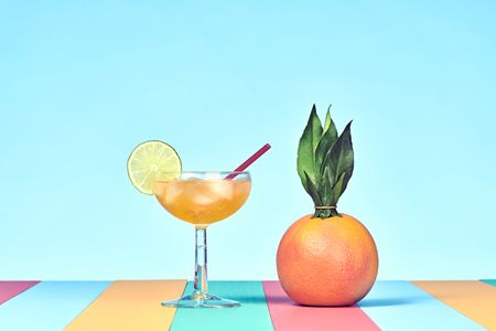 Tropical Grapefruit with Cocktail on Beach. Bright Summer Color. Trendy fashion Style. Hot summer Vibes. Creative Art. Fun party Mood. Minimal Stock Photo