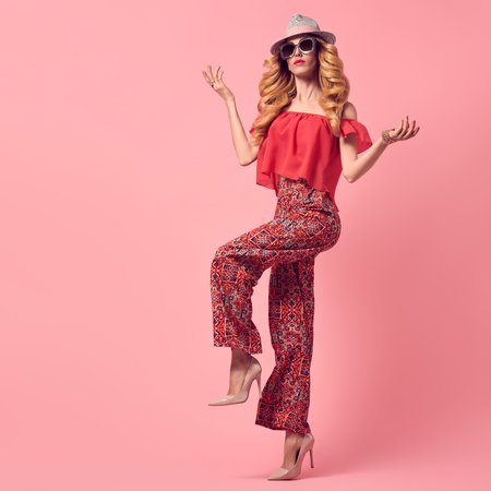 Fashion Young Woman in Summer Stylish Outfit. Wavy Hair, Trendy pants, Luxury Sunglasses, fashion Heels. Fashionable Beautiful Blond Lady. Slim Playful Model Girl Posing in Studio