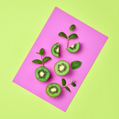 Kiwi Fresh Fruit with Mint leaves. Vegan Organic Food Concept. Creative Layout. Flat lay. Trendy fashion Style. Minimal Design Art. Hot Summer Vibes. Bright Purple Color.