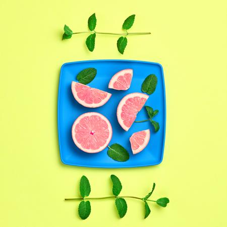 Orange Citrus Fresh Fruit with Mint leaves on plate. Vegan Organic Food Concept. Creative Flat lay. Trendy fashion Style. Minimal Design Art. Hot Summer Vibes. Bright Yellow Color. Zdjęcie Seryjne
