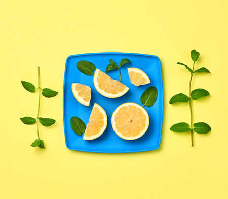Vegan juice Organic Concept. Yellow Lemon Fresh Fruit with Mint leaves on plate. Creative Flat lay. Trendy fashion Style. Minimal Design Art. Hot Summer Vibes. Bright Color.