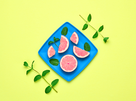 Pink Grapefruit Fresh Fruit with Mint leaves on plate. Vegan Organic Food Concept. Creative Flat lay. Trendy fashion Style. Minimal Design Art. Hot Summer Vibes. Bright Color.
