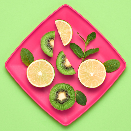 Lemon Kiwi Fresh Fruit with Green Mint leaves on plate. Vegan food Organic Concept. Creative Flat lay. Trendy fashion Style. Minimal Design Art. Hot Summer Vibes. Bright Color.
