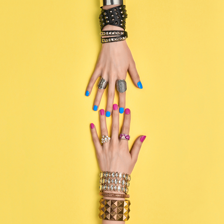 Fashion Accessories Set. Female hand, Stylish Trendy Jewelry, Glamor bracelets Ring. Minimal Design. Summer Girl Outfit. Hipster Essentials. Creative Art. Friendship concept on Yellow Zdjęcie Seryjne