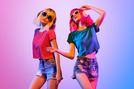 DJ Girl with Pink Blond Fashion Hairstyle Dance. Two Young Playful Hipster in Trendy Headphones. Sexy Woman in Sunglasses. Music vibrations, Night Clubbing. Creative Art Bright Light Foto de archivo - 102751027