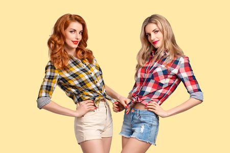 Two Happy Lovely Girls in Trendy Plaid Shirt Smiling on Yellow background. Young playful Sisters Friends Having Fun. Female Model in fashion Summer Outfit Posing in Studio