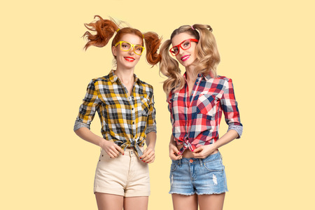 Two Sisters Twins Having Fun Jumping. Young Girls Friends Happy Laughing on Yellow background. Refined Woman in fashion Trendy Summer Plaid Shirt Fooling Around. Indoor