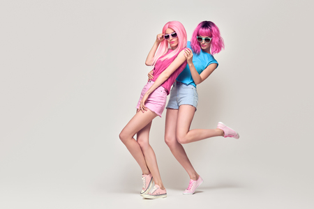 Full-length portrait Two Hipster Girls with Pink Fashion Hairstyle Having Fun Dance. Young Beautiful Pretty Model Woman in Stylish Trendy Summer Outfit. Crazy Sisters Friends