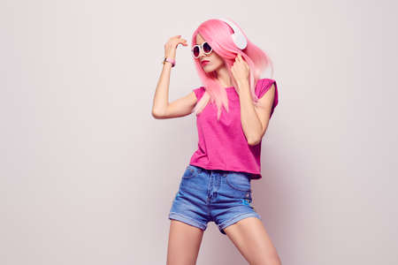 DJ Girl Hipster with Pink Fashion Hairstyle Dance. Young Playful Model Woman in Trendy Headphones Smiling Having Fun. Music vibrations, Clubbing. Cool Party Style