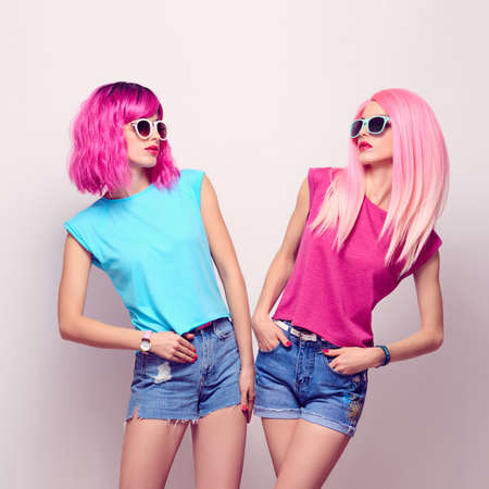 Fashion Portrait Two Girl. Hipster Woman with Pink Hairstyle. Young Beautiful Pretty Model in Stylish Trendy Summer Outfit. Cheeky Emotion.