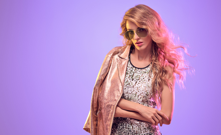 Gorgeous Blond woman wearing Stylish gold biker jacket and Sunglasses. High Fashion neon light. Glamorous sexy long-haired Model Girl in Trendy Outfit. Creative Bright Color Portrait