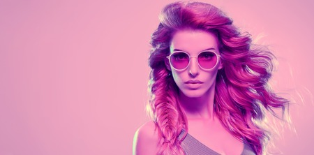 High Fashion neon light. Glamour Sexy Girl with Trendy Wavy Hairstyle, Stylish Sunglasses. Creative Bright Portrait, Pink Vanilla Color. Design Art concept, party vibrations Stock Photo