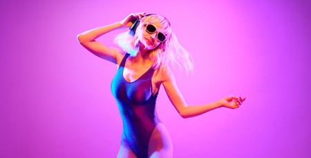 Shapely fashionable DJ girl dance enjoy music in colorful neon uv purple light. Rave house music night club vibes. High Fashion. Young blonde model woman relax enjoy dancing, neon makeup. Stock Photo