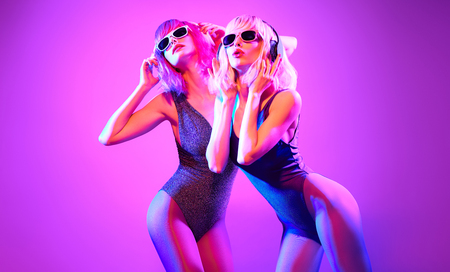 Fashion contemporary neon style. Two young graceful woman in party DJ bodysuit dance. Disco 80s 90s summer vibes. Adorable fashionable sexy girl with trendy makeup. Creative art purple neon color